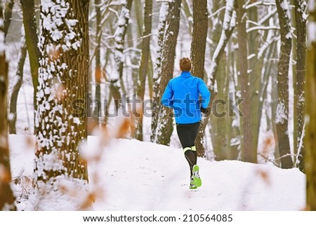 Young runner in winter jogging in forest - stock photo