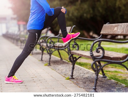 Young runner stretching before the city race - stock photo