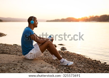 Young runner taking a break, enjoying nature and listening to the music. - stock photo