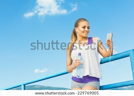 Young runner woman outdoors with smartphone, earphones and bottle of water smiling creating a running playlist and taking a break. Active lifestyle concept. - stock photo