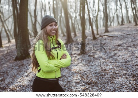 Young runner woman resting in forest after workout