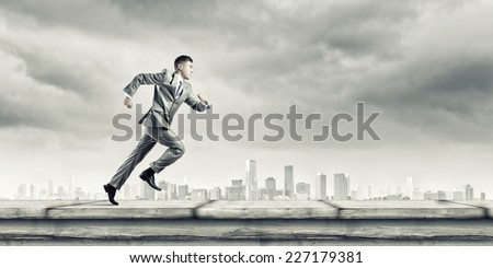 Young running businessman with colorful splashes in hand - stock photo