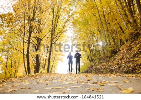 Young running couple jogging in autumn nature - stock photo