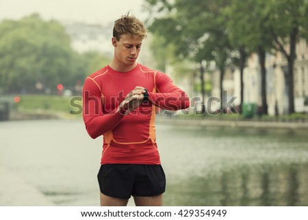 Young running man looking at his heart rate monitor sports smart watch.
