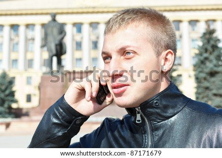 Young Russian handsome man calling on mobile phone in Russia - stock photo