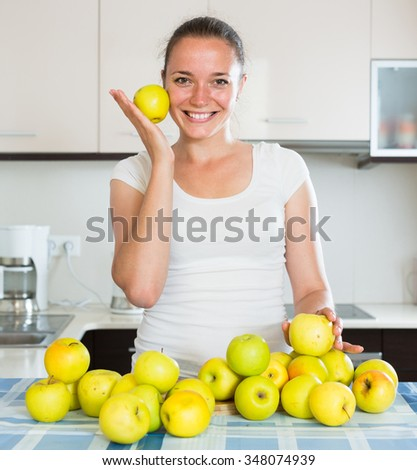 Young russian woman cooking dish from apples in kitchen