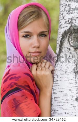 Young russian woman in headscarf near birch - stock photo