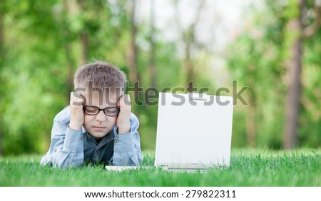 young sad boy with laptop computer on green grass in the park - stock photo