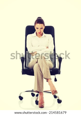 Young sad business woman sitting on a chair. Isolated on white. - stock photo