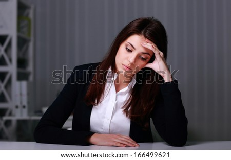 Young sad businesswoman sitting at the table on her workplace in office - stock photo