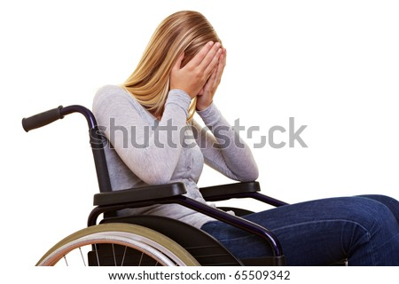 Young sad disabled woman in wheelchair crying - stock photo