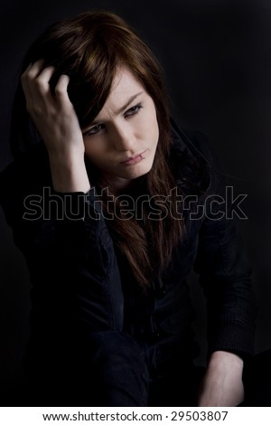 Young sad girl alone in a dark room - stock photo