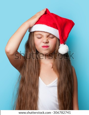 Young sad girl in Santas hat on blue background. - stock photo