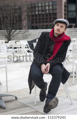 young sad man wearing check cap and red scarf  and red scarf sitting at the street cafe waiting for order - stock photo