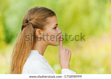 Young sad nice woman puts finger to her lips, against background of autumn park.