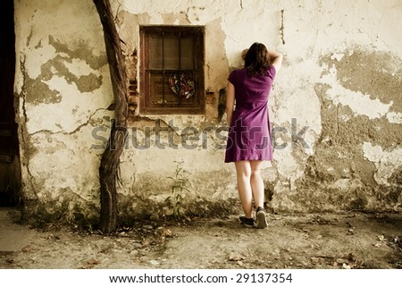 Young sad woman crying in wall - stock photo