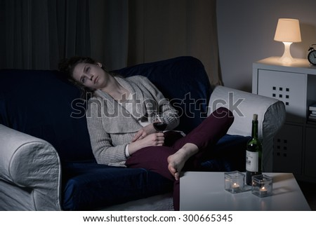 Young sad woman drinking wine alone in the evening - stock photo