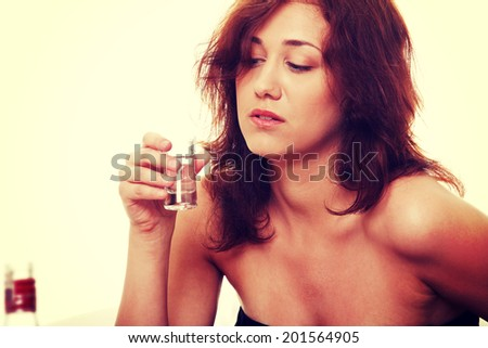 Young sad woman in depression, drinking alcohol - stock photo