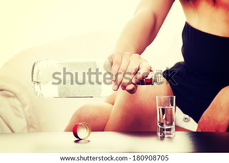 Young sad woman in depression, drinking alcohol (vodka)  - stock photo