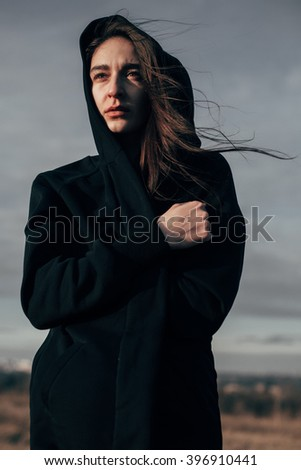 Young sad woman in windy weather against a gray sky - stock photo