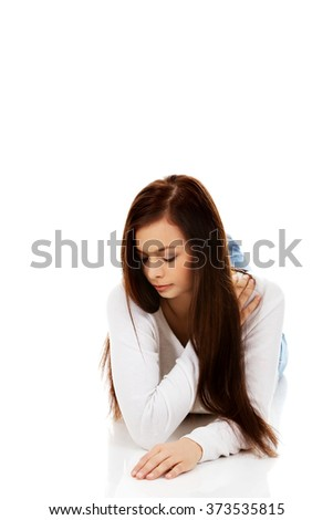 Young sad woman lies on the floor - stock photo