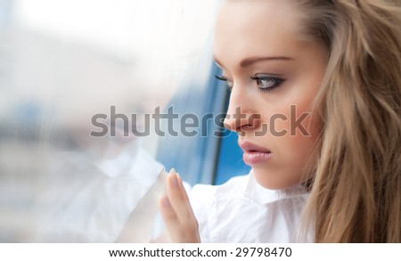 Young sad woman look out a window - stock photo