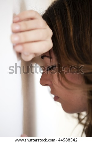Young sad woman portrait against wall - stock photo