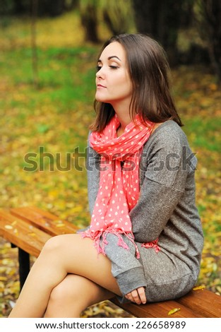 Young sad woman portrait sitting on a bench in evening park. - stock photo