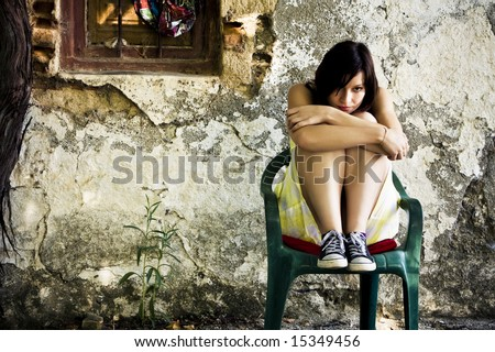 Young sad woman sited on dirty place. - stock photo