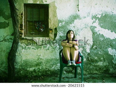 Young sad woman sitting in old dirty place - stock photo