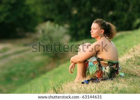 young sad woman sitting on grass