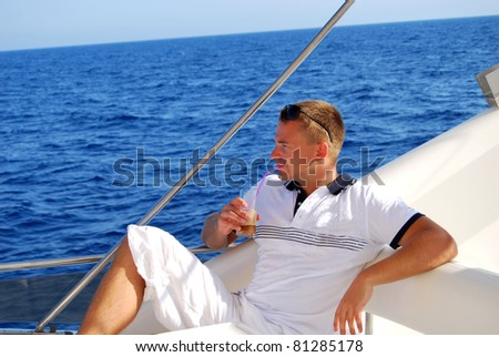 Young Sailor relaxing happily on the vacation sailboat yacht and drinking cold frappe having a rest on summer boat over blue ocean background - stock photo