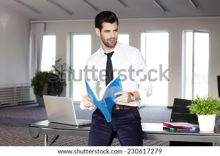 Young sales man holding files in hands and sitting at office. Business people.  - stock photo