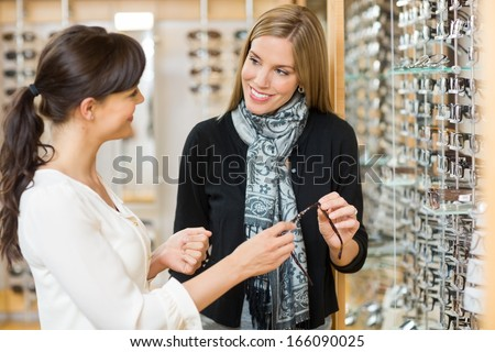 Young salesgirl and female customer holding glasses while looking at each other in shop - stock photo