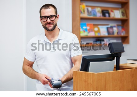 Young salesman at the checkout in a bookstore - stock photo