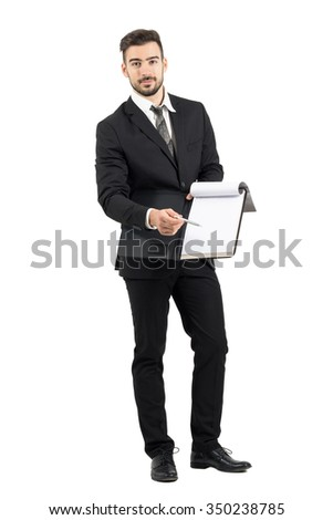 Young salesman in suit pointing signature space with pencil offering contract. Full body length portrait isolated over white studio background.