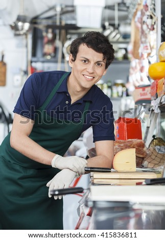 Young Salesman Leaning On Counter In Cheese Shop
