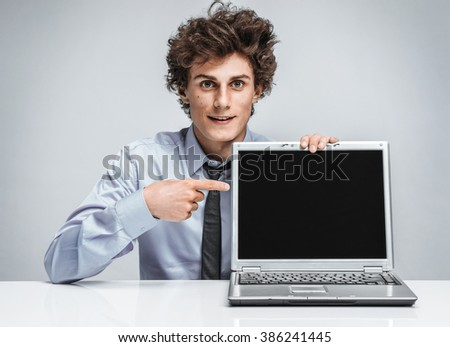 Young salesman showing at screen laptop. Modern businessman at the workplace working with computer. Business concept  - stock photo