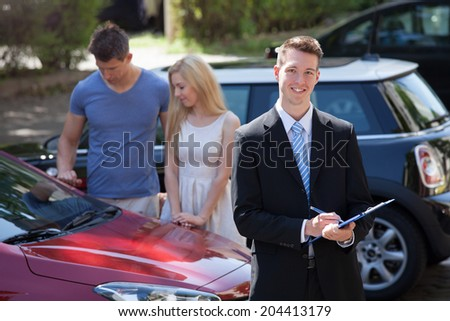 Young salesman writing on clipboard with couple looking at new car in background - stock photo