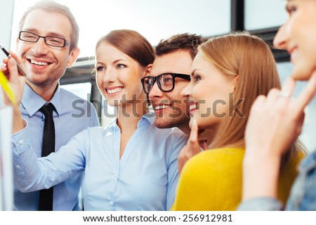 Young salespeople analyzing their sales on a board - stock photo