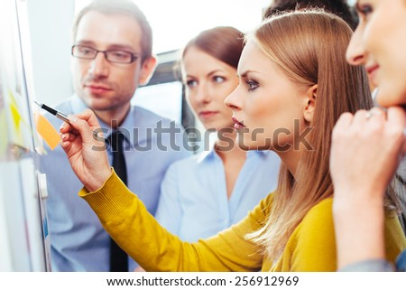 Young salespeople looking at some data presented on a board - stock photo