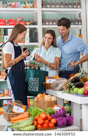 Young saleswoman showing vegetable packet to couple in supermarket - stock photo