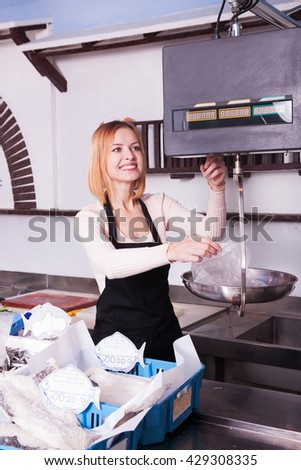 young saleswoman weighing fresh fish in shop - stock photo