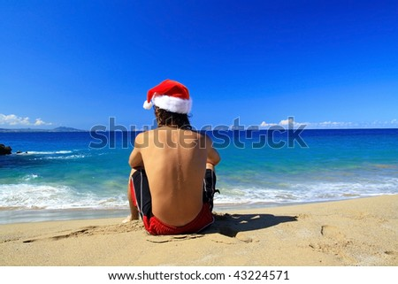 Young Santa Claus from the back on beach of ocean - stock photo