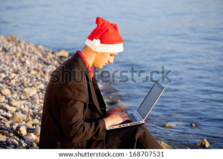 young santa claus sitting on beach - stock photo