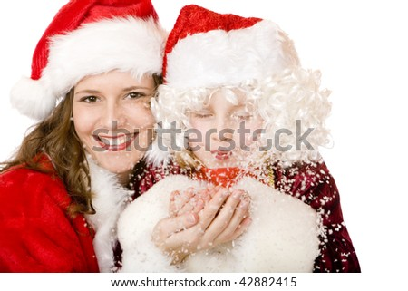 Young Santa Claus woman and child in Santa costume are blowing snow from palm. Isolated on white. - stock photo