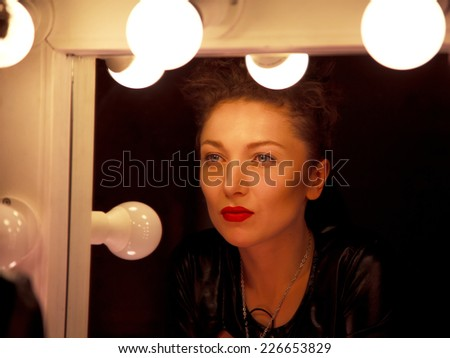 Young sassy woman with red lips in the dressing room in the dark before a mirror  - stock photo