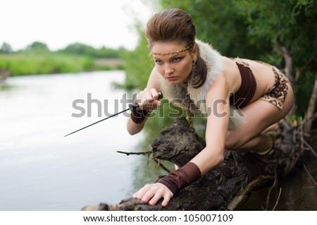 Young savage hunt on the river - stock photo
