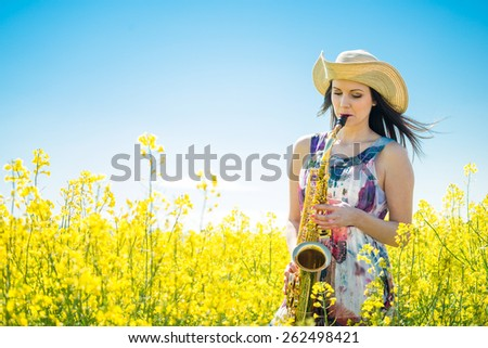 Young  saxophonist (woman) playing saxophone in blossoming rapeseed field - stock photo