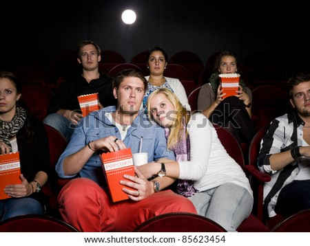 Young Scared Couple at the Movie Theater eating popcorn - stock photo